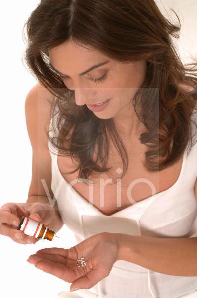 Frau schüttet Tabletten aus Fläschchen in die Hand