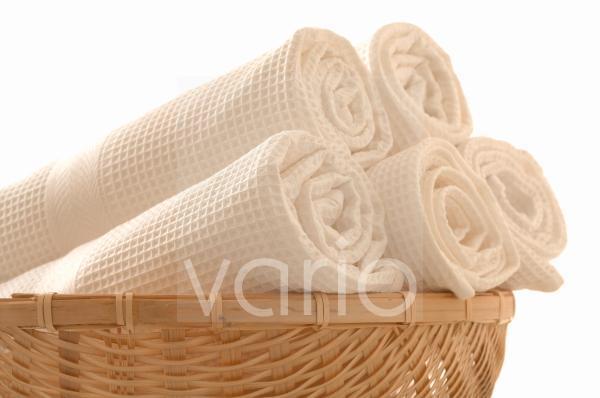 Ein Korb voll weißer Piqué-Handtücher