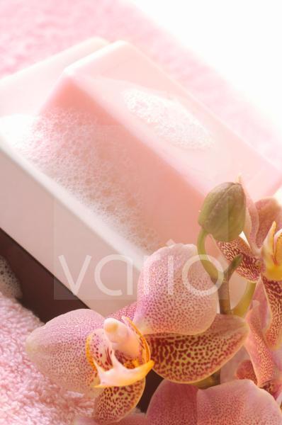 Schaumige Seife in einer Seifenschale mit einer Orchideenblüte dekoriert