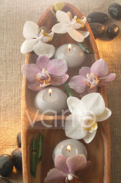 Kerzen und Orchideenblüten in Holzschale