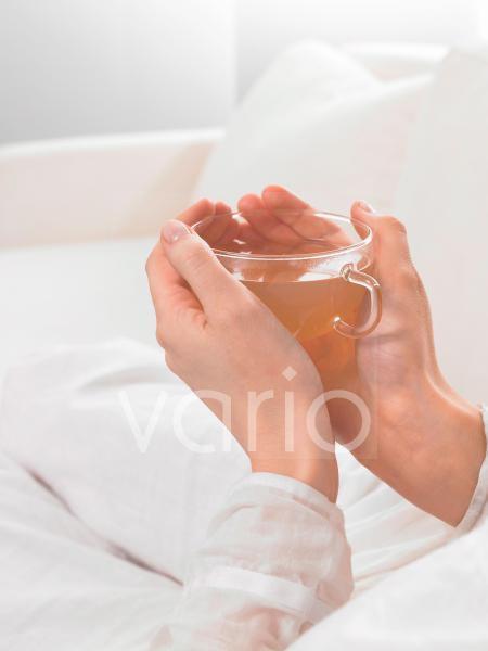 Teeglas wird von zwei Händen umfasst