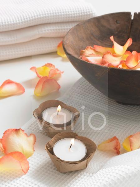 Rosenblütenblätter in einer Holzschale und Teelichter auf Waffel-Piqué Tüchern