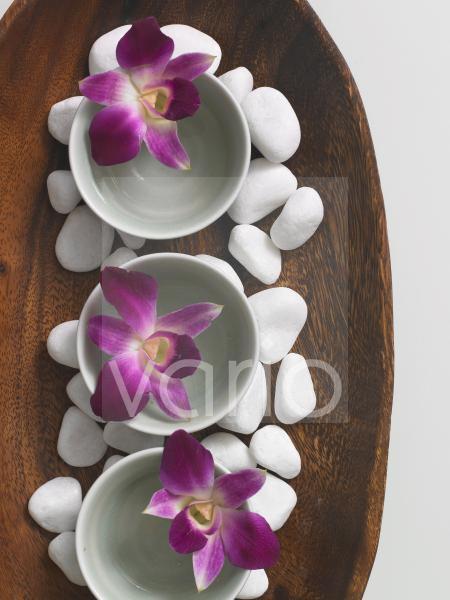 Holzschale dekoriert mit Kieselsteinen und Blüten in Porzellanschälchen