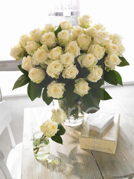 Weißer Rosenstrauß mit Geschenken