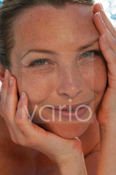 Gesicht von blonder Frau; stützt Kopf auf Hände