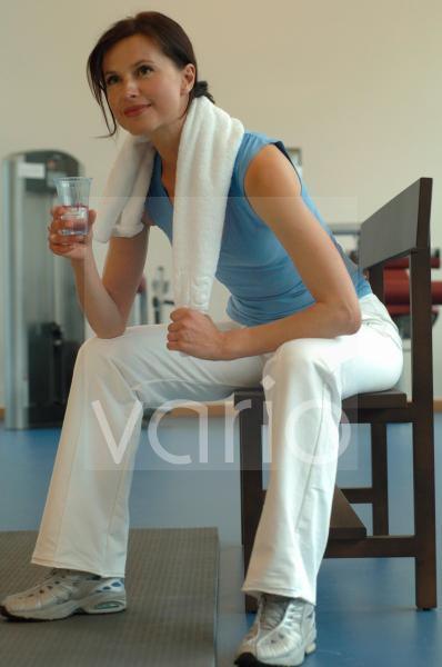 Frau im Fitnessstudio trinkt ein Glas Wasser