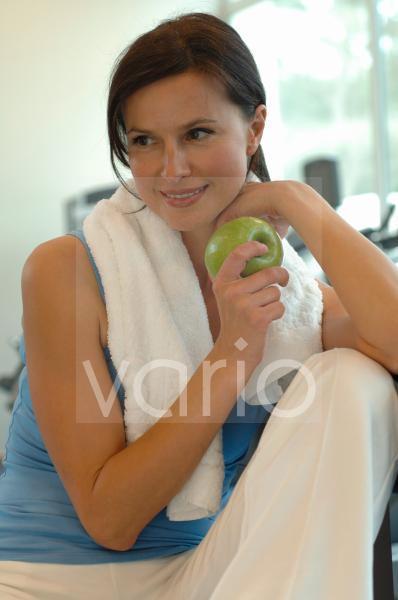Frau im Fitnessstudio mit Apfel