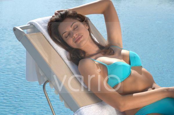 Frau im Liegestuhl am Swimmingpool