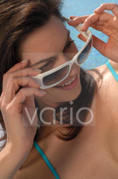 Frau setzt Sonnenbrille auf