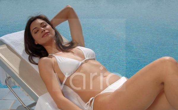 Frau sonnt sich am Swimming Pool