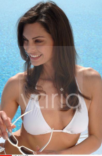 Frau auf Liege am Swimming Pool mit Sonnenbrille