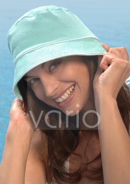Frau mit Sonnenhut am Swimmingpool