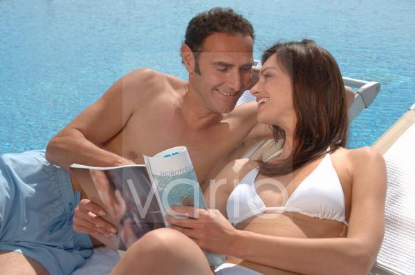 Paar amüsiert sich am Swimmingpool mit Zeitschrift