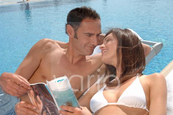 Paar relaxed am Swimmingpool mit Zeitschrift
