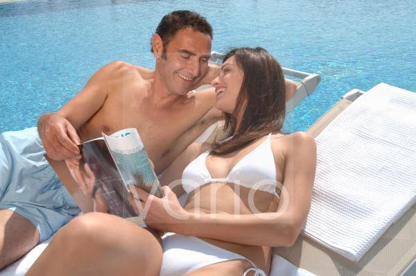 Paar amüsiert sich am Swimmingpool mit einer Zeitschrift