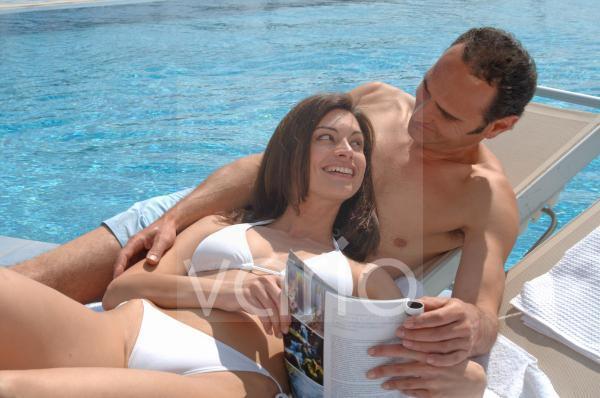 Paar liest am Swimmingpool in einer Zeitschrift