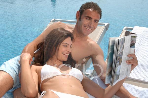Paar am Swimming Pool liest eine Zeitschrift