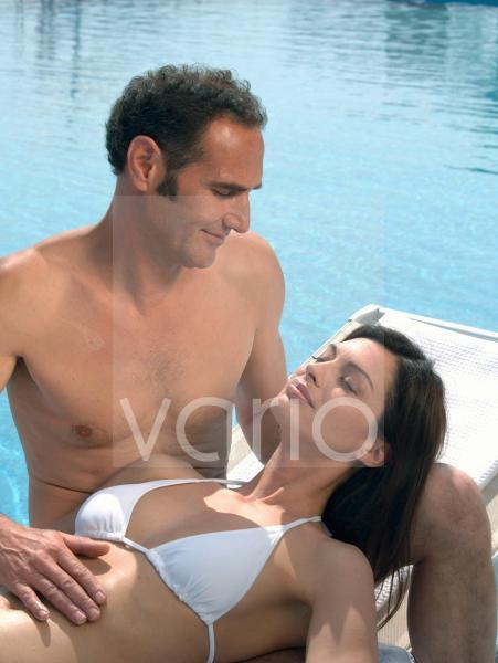 Mann streichelt Frau am Swimmingpool den Bauch