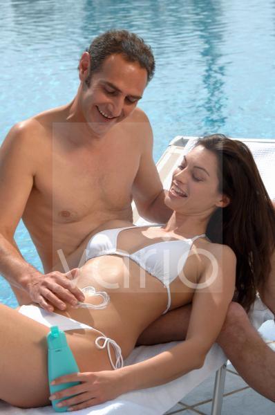 Mann cremt Frau den Bauch ein