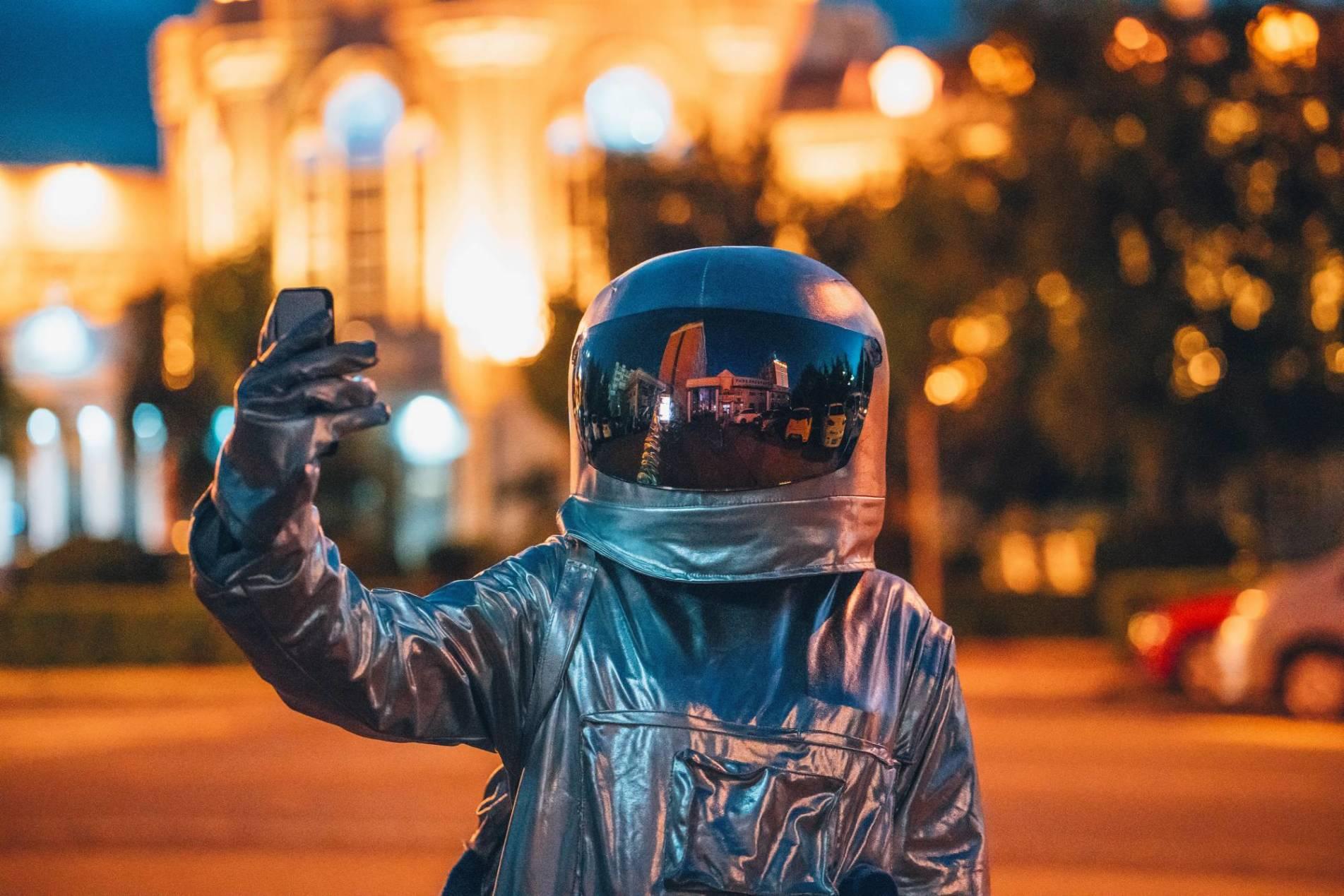 VP 6269648,  Spaceman on a street in the city at night holding smartphone  [Urhebervermerk: Vasily Pindyurin/Westend61/vario images]  [JEGLICHE VERWENDUNG nur gegen HONORAR und BELEG. URHEBER/AGENTURVERMERK wird gemaess Paragraph 13 UrhG und unserer AGB ausdruecklich verlangt. Es gelten ausschliesslich unsere AGB. Tel: +49-(0)228-935650, www.vario-images.com]