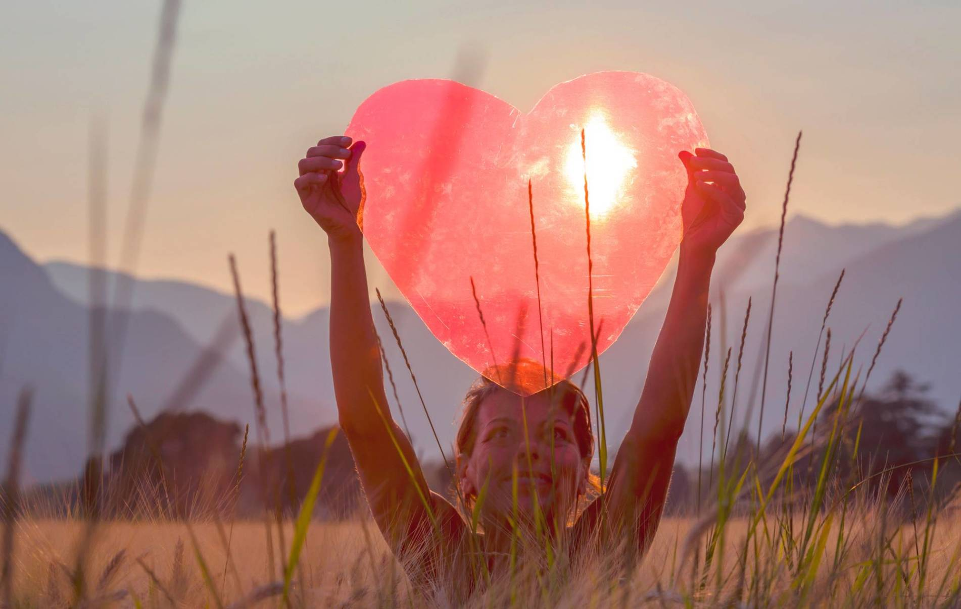 A Woman Holds Up A Red Heart With The Sun To Shine Through